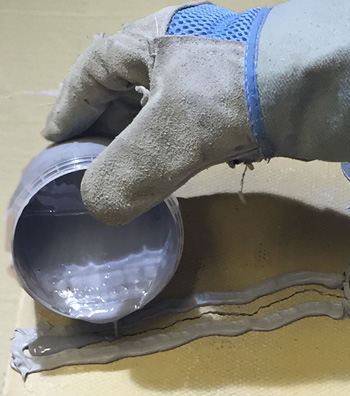 Pouring epoxy resin into crack to fix repair